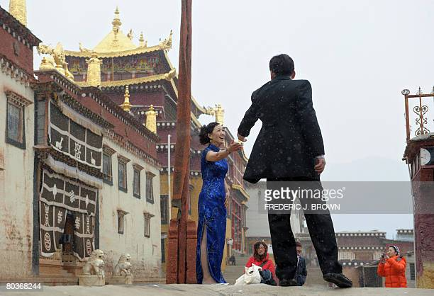 By Robert Saiget Visiting tourists from Hong Kong have their wedding photos taken under a light snowfall at the Ganden Sumtseling Monastery in...