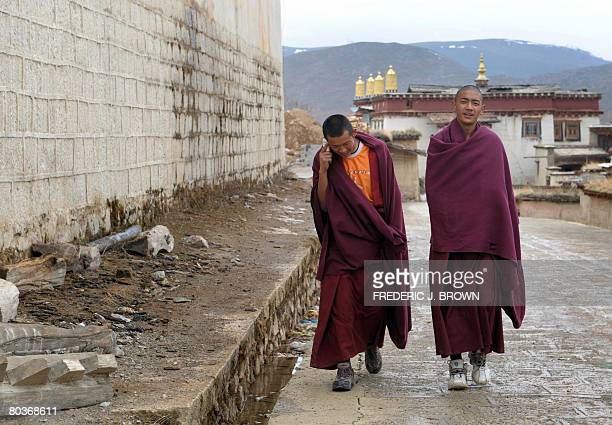 By Robert Saiget With their basketball sneakers and mobile phone, Tibetan Buddhist monks are seen walking at the back of the Ganden Sumtseling...