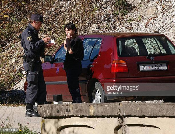 By Rusmir Smajilhodzic Slovenian border policeman strictly checks papers of Croatian driver at blocked local bridge over Kupa river which makes a...