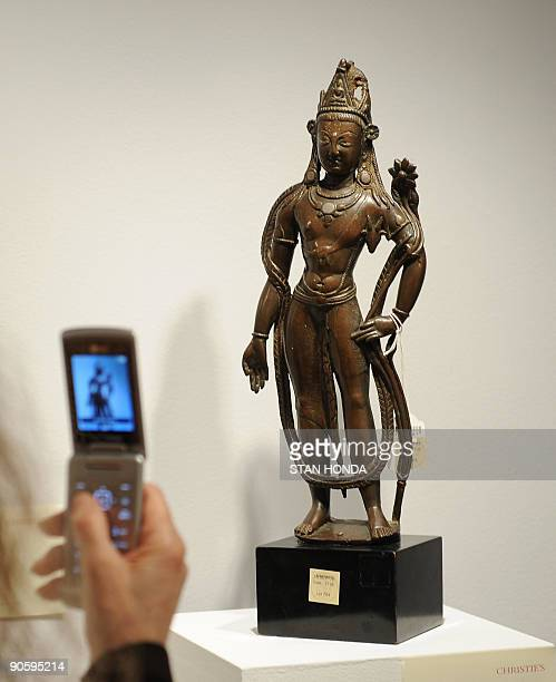 STORY by Sebastian Smith LifestyleUSartauction A visitor takes a cell phone photograph of a silver inland bronze figure of Avalokiteshvara from...