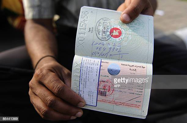 STORY 'FINANCEECONOMYBANGLADESHMIGRATION' by Shafiq Alam Bangladeshi migrant labourer Mohammed Sohid poses with his passport outside the arrivals...