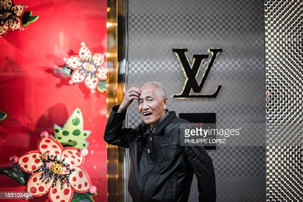FOCUS by Stephen Coates In this picture taken on September 26 a Chinese mainland tourist scratches his head in front of a luxury shop in Hong Kong...
