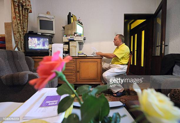 STORY by Suzana Markovic Picture taken on June 6 shows Dusan Trifunovic sitting in front of a computer in the safe house for abused men in central...