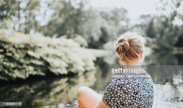 by the waters edge - opgestoken haar stockfoto's en -beelden