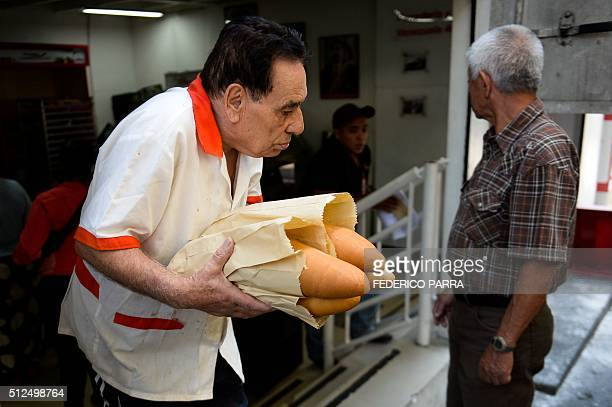 STORY by Valentina Oropeza and Ernesto Tovar A man walks out of one of the bakeries still offering some bread with four baguettes in Caracas on...