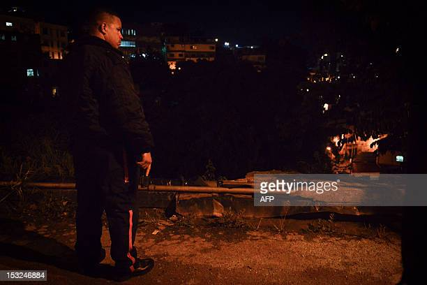 STORY by Valeria Pacheco A municipal police officer stands watch in the impoverished Petare neighbourhood one of Caracas' most dangerous slums on...