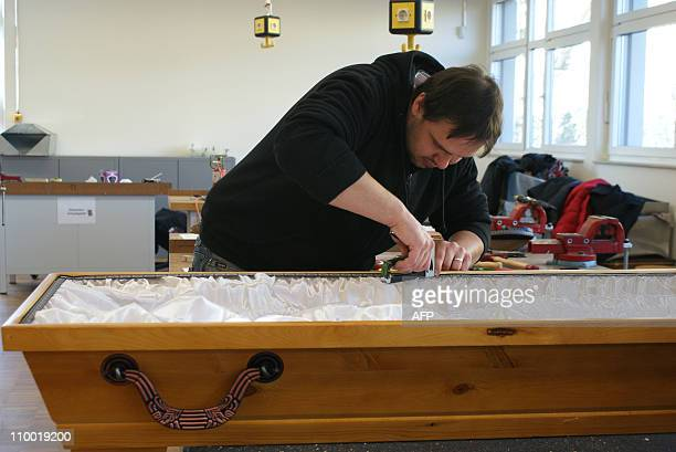 STORY by YANNICK PASQUET Christian Richter student at Germany's 'funeral school' works on a coffin on February 23 2011 at the school's workshop in...