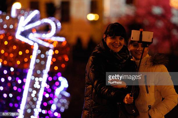 POLAND Bydgoszcz December 8 2016 Two young women are seen taking selfies in front of a Christmas display on the old market square Christmas spending...