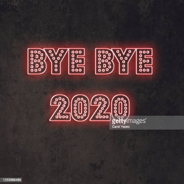 bye bye 2020 text in neon lights in black background - 2020 stock pictures, royalty-free photos & images