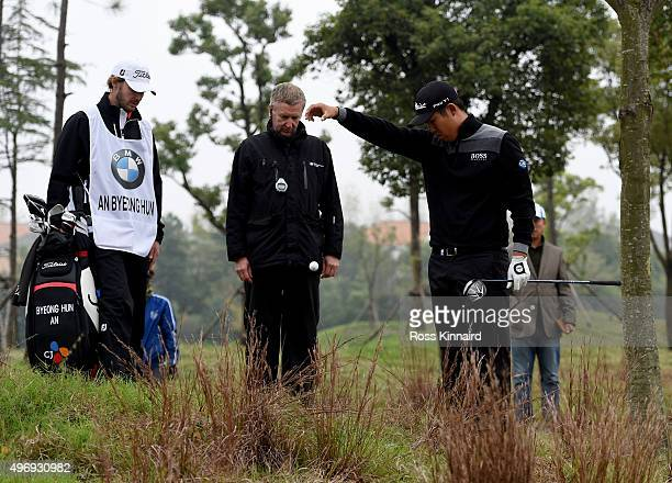 Byeong Hun An of Korea takes a free drop near the 18th green with the help of European Tour referee Mark Litton during the second round of the BMW...