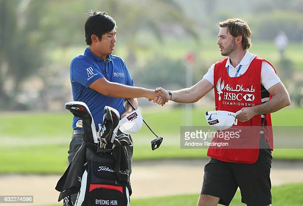 Byeong Hun An of South Korea shakes hands with his caddie Dan Parrott on the 18th green during the third round of the Abu Dhabi HSBC Championship at...