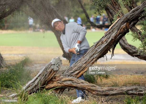 Byeong Hun An of the International Team plays his second shot on the 18th hole in his match with Adam Scott against Tony Finau and Matt Kuchar of the...