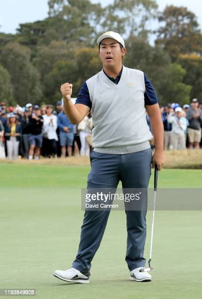Byeong Hun An of the International Team reacts as he holes a putt on the 17th hole in his match with Joaquin Niemann against Matt Kuchar and Tony...