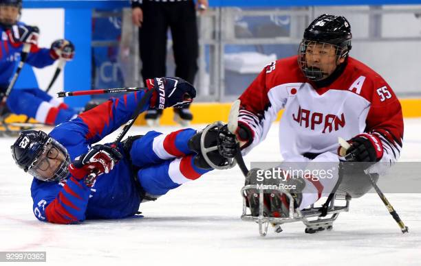 Byeong Seok Cho of Korea battles for the puck with Kazuhiro Takahashi of Japan in the Ice Hockey Preliminary Round Group A game between South Korea...
