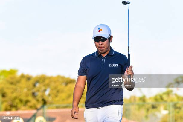 ByeongHun An of Korea raises his putter to fans after making a birdie putt on the 17th hole green during the second round of the Arnold Palmer...