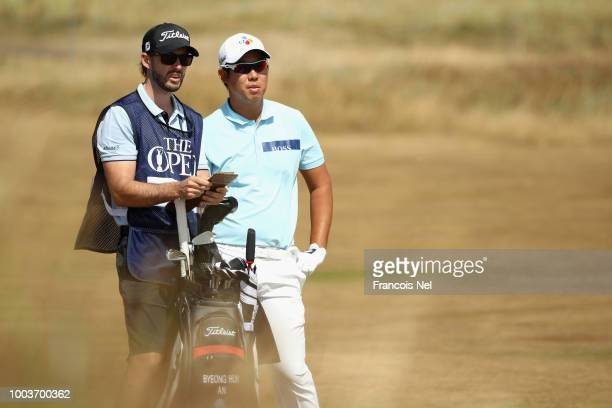 ByeongHun An of Korea waits with his caddie Daniel Parratt in the second fairway during the final round of the 147th Open Championship at Carnoustie...