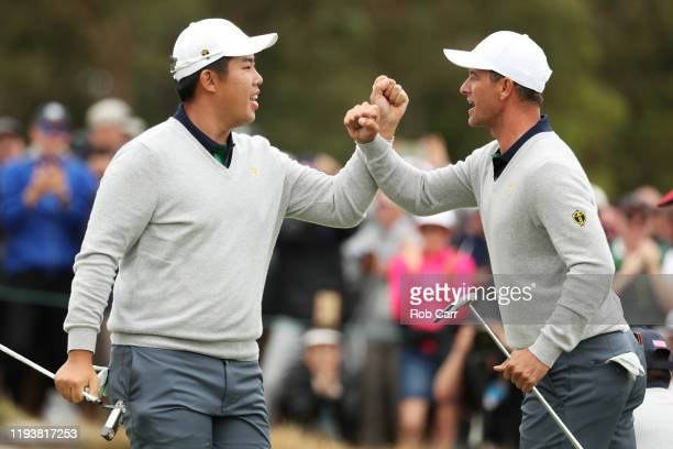 Byeong-Hun An of South Korea and the International team and Adam Scott of Australia and the International team react on the 17th green during...
