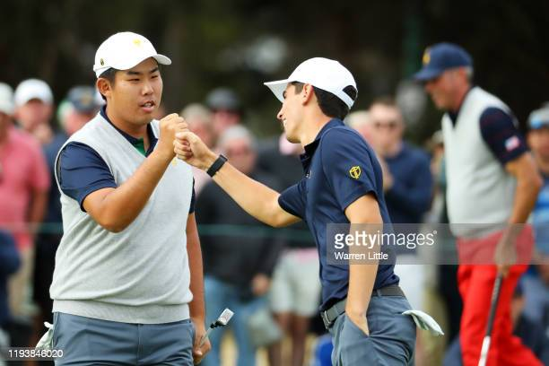 ByeongHun An of South Korea and the International team and Joaquin Niemann of Chile and the International team celebrate on the 17th green during...