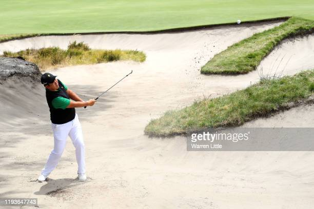 Byeong-Hun An of South Korea and the International team plays a shot from a bunker on the ninth hole during Friday foursome matches on day two of the...