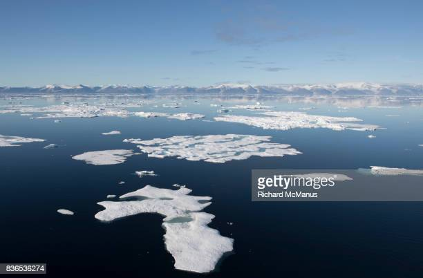 bylot island behind the sea ice in pond inlet. - nunavut stock pictures, royalty-free photos & images