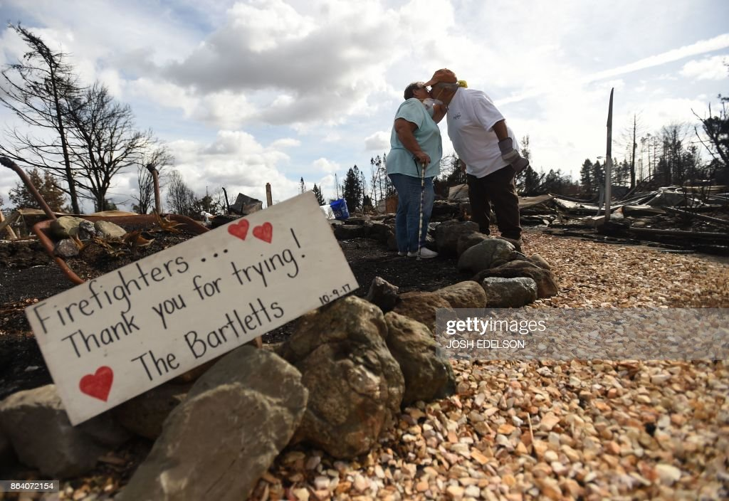 TOPSHOT - Byron (R) and Joanne Bartlett (L) pose for a photo in front of a sign they made for firefighters at as they search for remains at their burned residence in the Coffey Park area of Santa Rosa, California on October 20, 2017. Residents are being allowed to return to their burned homes on October 20 to grieve and search through remains. Around 5,700 homes and businesses have been destroyed by the fires, the deadliest in California's history. /