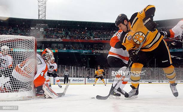 Byron Bitz of the Boston Bruins takes a shot against Michael Leighton of the Philadelphia Flyers during the 2010 Bridgestone Winter Classic at Fenway...