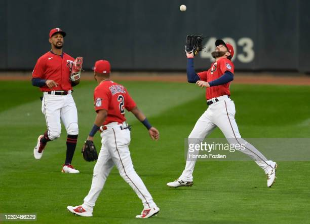 Byron Buxton and Luis Arraez of the Minnesota Twins look on as Jake Cave makes a catch in right field of the ball hit by Adam Frazier of the...
