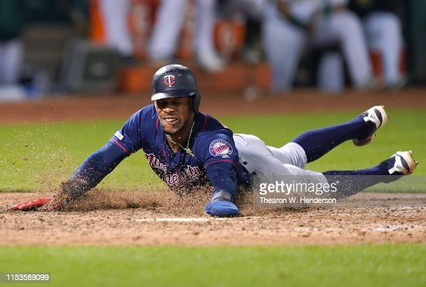 Byron Buxton of the Minnesota Twins dives at home plate scoring the go ahead run against the Oakland Athletics in the top of the 12th inning of a...