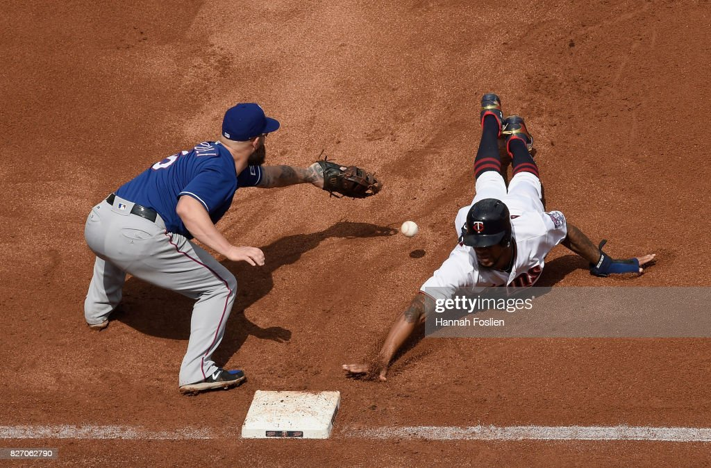 Byron Buxton #25 of the Minnesota Twins dives back safely to first base as the ball gets past Mike Napoli #5 of the Texas Rangers during the fourth inning of the game on August 6, 2017 at Target Field in Minneapolis, Minnesota. The Twins defeated the Rangers 6-5.