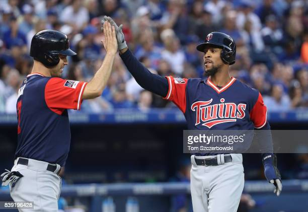 Byron Buxton of the Minnesota Twins is congratulated by Joe Mauer after scoring a run in the third inning during MLB game action against the Toronto...