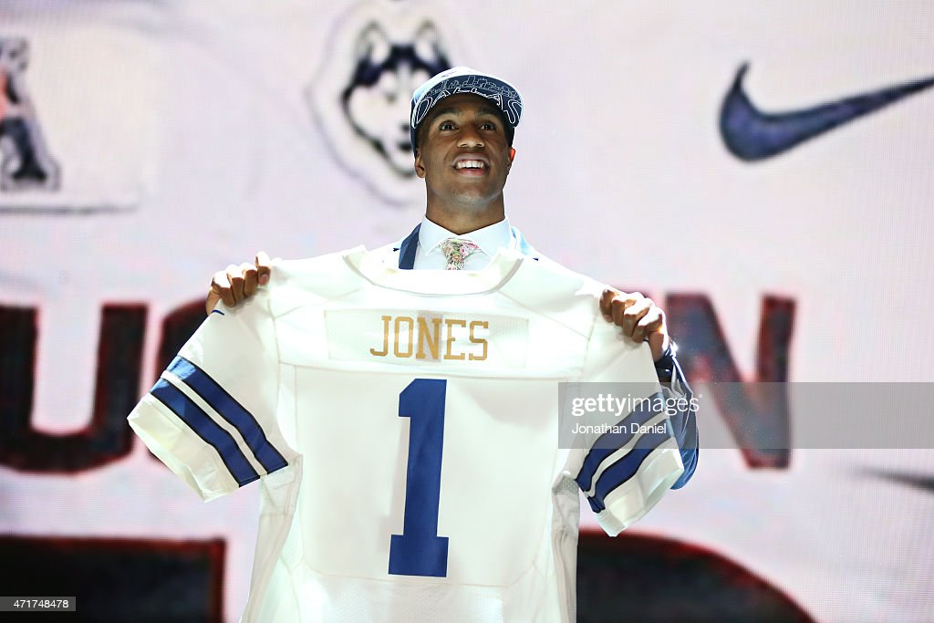 Byron Jones of the Connecticut Huskies holds up a jersey after being picked #27 overall by the Dallas Cowboys during the first round of the 2015 NFL Draft at the Auditorium Theatre of Roosevelt University on April 30, 2015 in Chicago, Illinois.