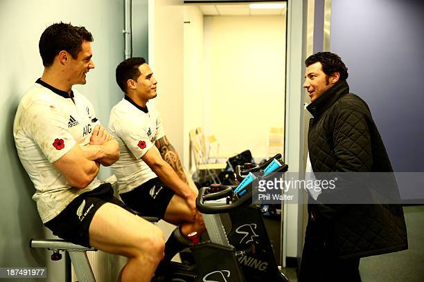 Byron Kelleher speaks with Dan Carter and Aaron Smith of the All Blacks in the dressing room following the international test match between France...