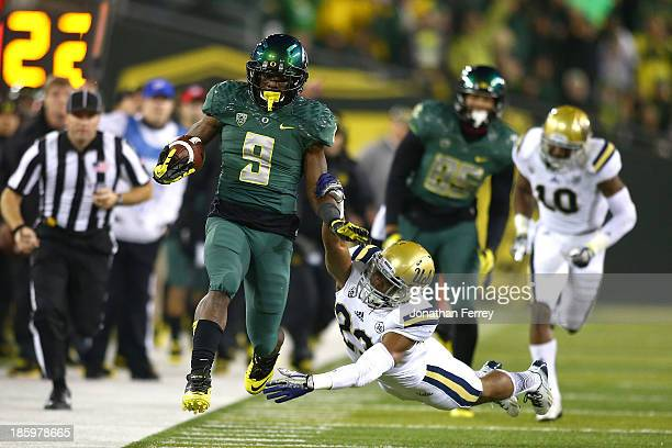 Byron Marshall of the Oregon Ducks runs against Tyler Foreman of the UCLA Bruins on October 26 2013 at the Autzen Stadium in Eugene Oregon