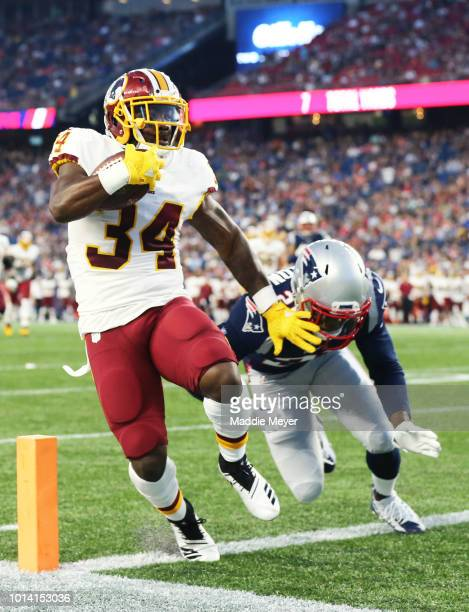 Byron Marshall of the Washington Redskins runs in for a touchdown past Duron Harmon of the New England Patriots during the preseason game between the...