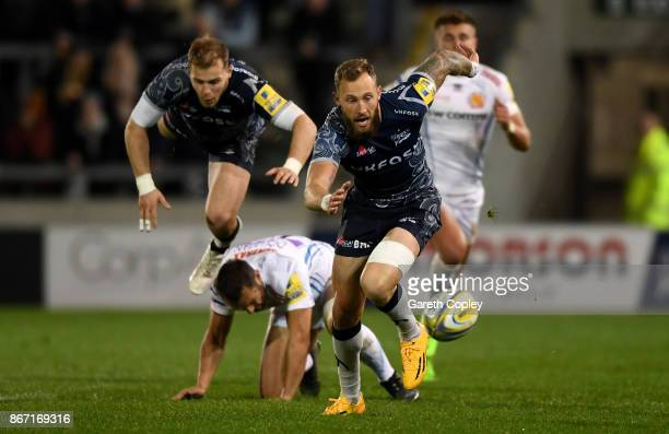 Byron McGuigan of Sale breaks down field past Will Addison and Phil Dollman of Exeter during the Aviva Premiership match between Sale Sharks and...