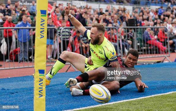 Byron McGuigan of Sale Sharks celebrates after scoring their first try despite the efforts of Nathan Earle of Saracens during the Aviva Premiership...
