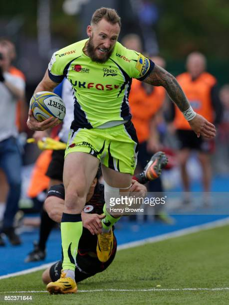 Byron McGuigan of Sale Sharks goes past the challenge from Henry Taylor of Saracens during the Aviva Premiership match between Saracens and Sale...