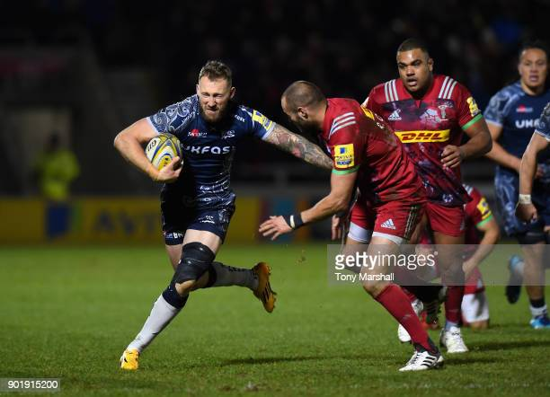 Byron McGuigan of Sale Sharks is tackled by Ross Chisholm of Harlequins during the Aviva Premiership match between Sale Sharks and Harlequins at AJ...