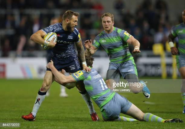 Byron McGuigan of Sale Sharks is tackled by Simon Hammersley of Newcastle Falcons during the Aviva Premiership match between Sale Sharks and...