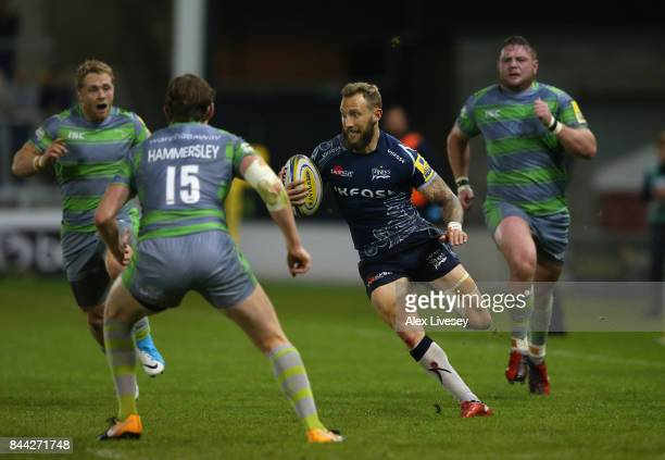 Byron McGuigan of Sale Sharks runs at Simon Hammersley of Newcastle Falcons during the Aviva Premiership match between Sale Sharks and Newcastle...