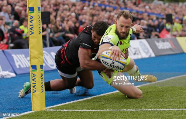 Byron McGuigan of Sale Sharks scores their first try despite the efforts of Nathan Earle of Saracens during the Aviva Premiership match between...