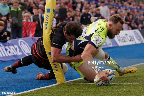 Byron McGuigan of Sale Sharks scores their second try despite the efforts of Henry Taylor of Saracens during the Aviva Premiership match between...