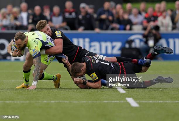 Byron McGuigan of Sale Sharks tackled by Nick Isiekwe and Liam Williams of Saracens during the Aviva Premiership match between Saracens and Sale...