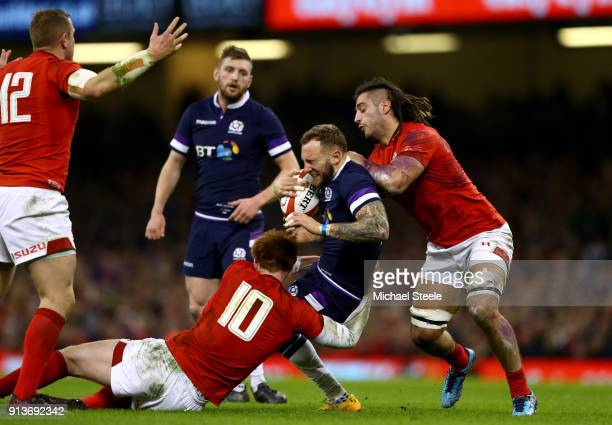 Byron McGuigan of Scotland is tackled by Josh Navidi of Wales and Rhys Patchell of Wales during the Natwest Six Nations round One match between Wales...