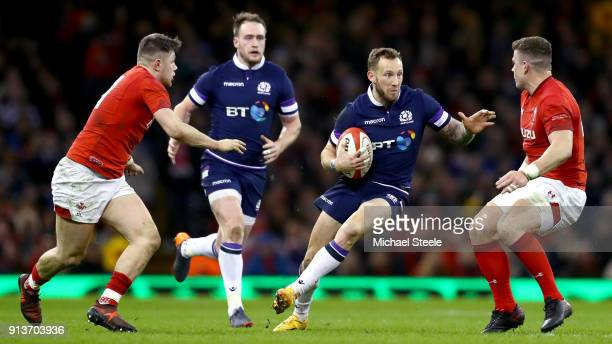 Byron McGuigan of Scotland runs with the ball towards Scott Williams of Wales during the Natwest Six Nations round One match between Wales and...