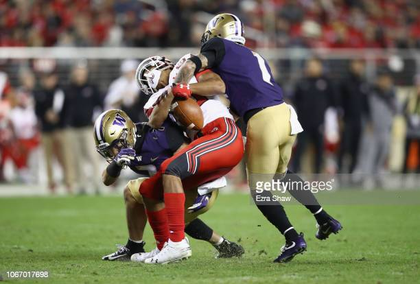 Byron Murphy and Taylor Rapp of the Washington Huskies hit Solomon Enis of the Utah Utes and forced him to drop the ball during the Pac 12...