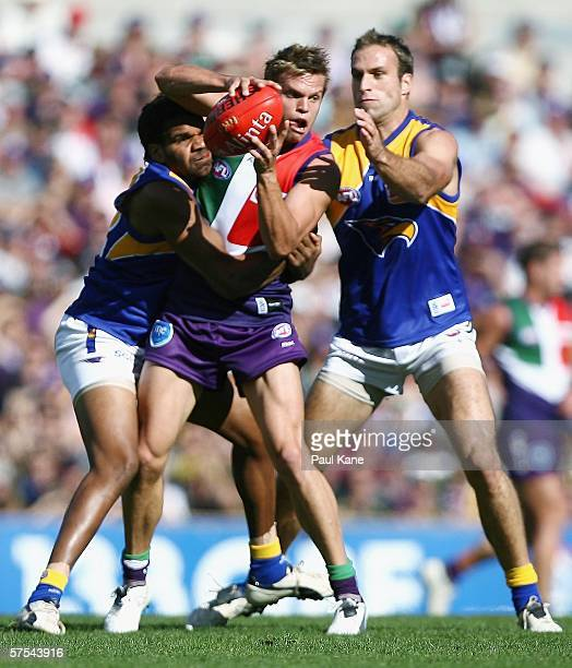 Byron Schammer of Fremantle is tackled by Ashley Sampi and Chris Judd of the Eagles during the round six AFL match between the Fremantle Dockers and...