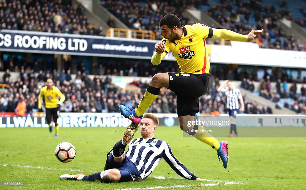 Byron Webster of Millwall (L) attempts to block Troy Deeney of Watford (R) shot during The Emirates FA Cup Fourth Round match between Millwall and Watford at The Den on January 29, 2017 in London, England.