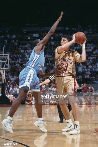 Byron Wells, Forward for the Florida State Seminoles holds the ball as Pat Sullivan of the University of North Carolina Tar Heels attempts to block...