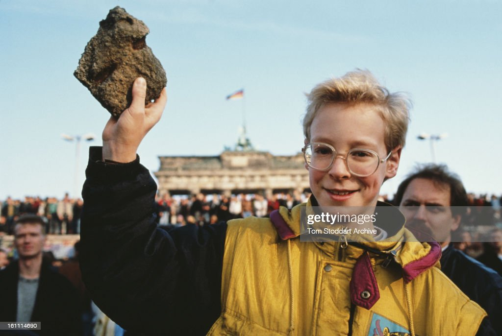 A bystander holds a souvenir chunk of masonry from the Berlin Wall, during the Fall of the Berlin Wall, 10th November 1989.